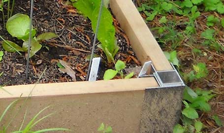 Hardware anchors the side of a raised bed