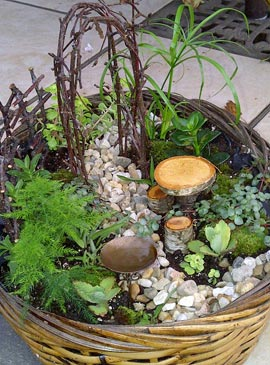 This fairy garden uses twigs for an arbor and is built in a wicker basket.