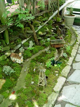 A working train runs through this miniature village that uses moss to simulate grassy fields.