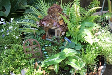 This fairy garden is an outdoor, in-ground model that uses a traditional woodland theme.